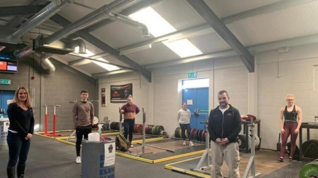 Coach and Lifters stand socially distanced for photo in HAWFC