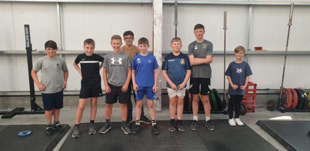 School-age boys smiling in their Weightlifting Club
