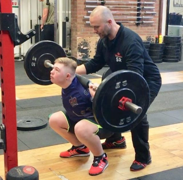 Coach Simon Roach spotting a young lifter performing a backsquat