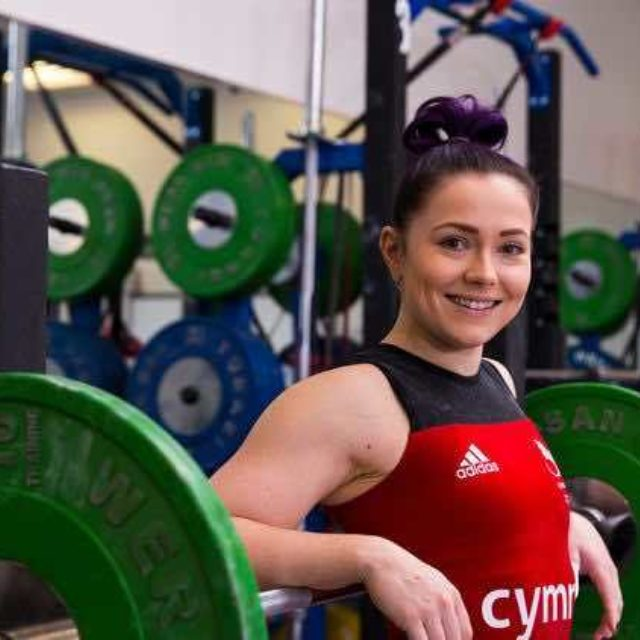 Christie Williams in Welsh Lifting suit smiles for a shot with a loaded weightlifting bar