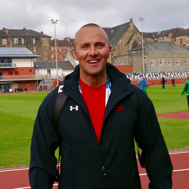 Simon Roach portrait with athletic track background